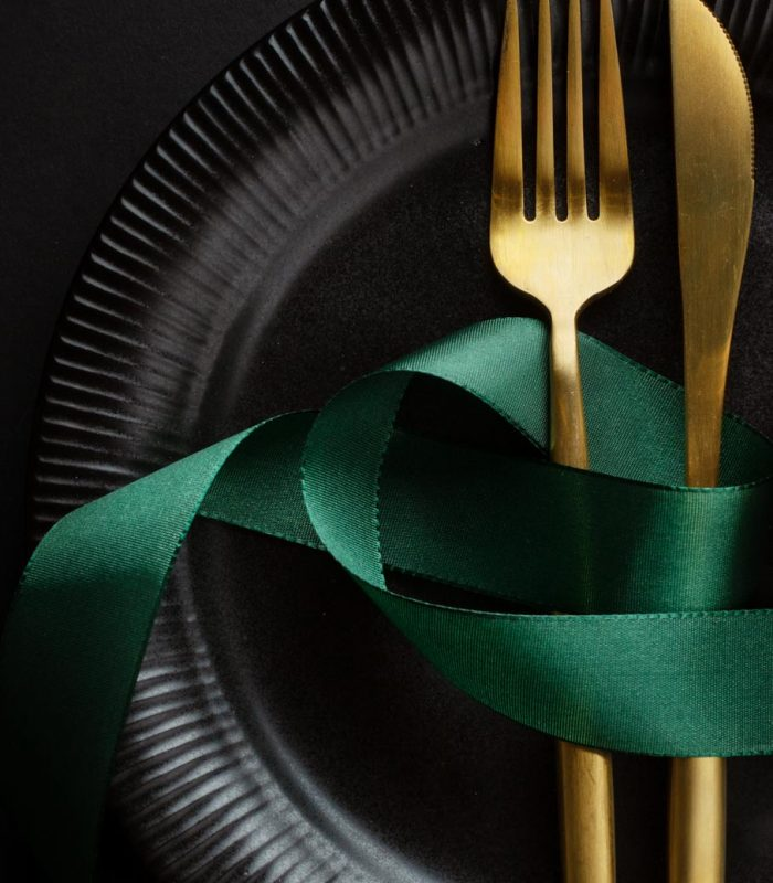 Christmas golden cutlery on plate with bauble and ribbon on dark background. Banner